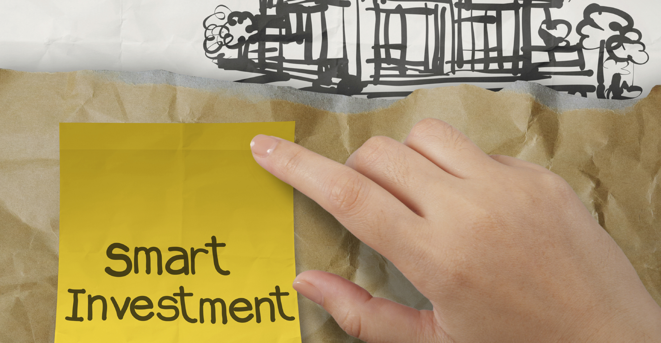 hand holding smart investment sticky note with  house on wrinkle